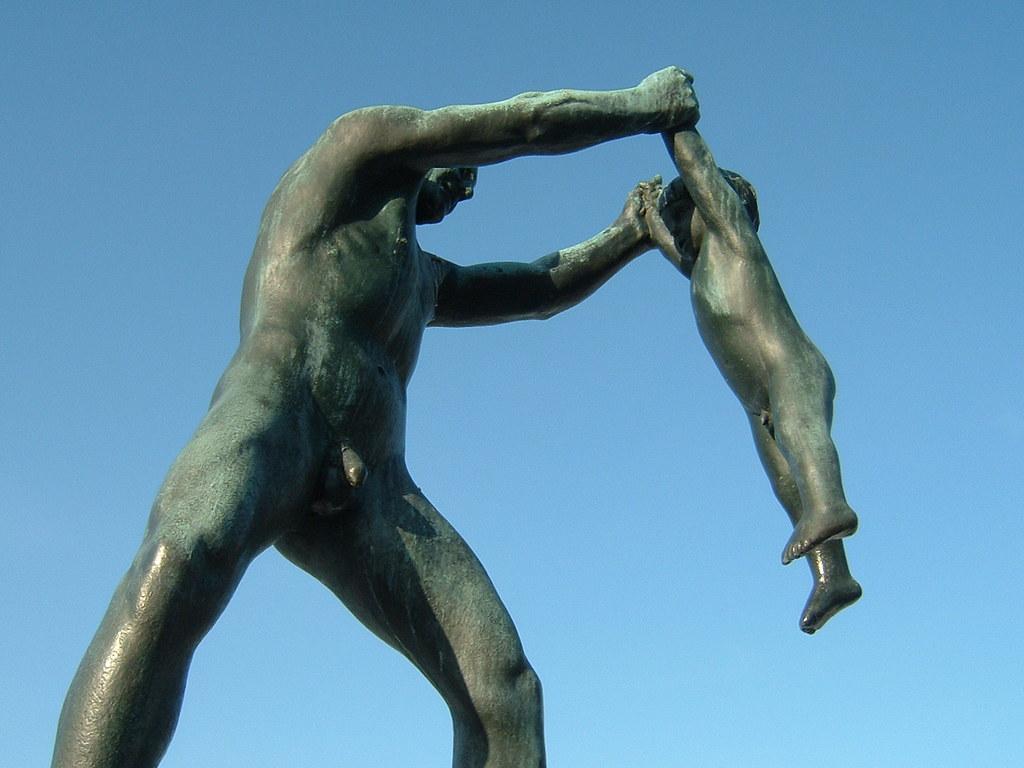 Un padre de bronce juega a columpiar a su hijo de corta edad
