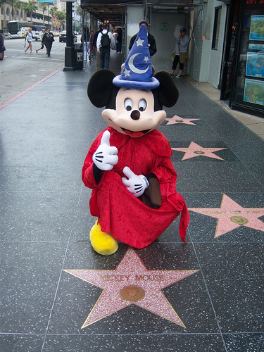 mickey mouse poses with his star on the hollywood walk of