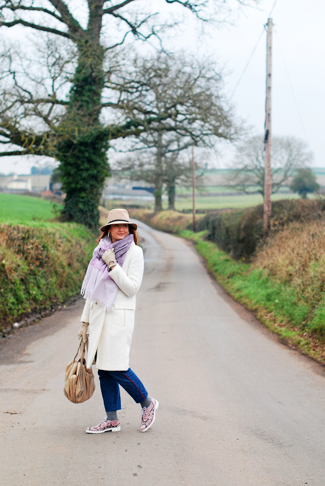 Cold weather outfit: Long white wool coat \ oversized lilac scarf \ camel fedora \ dark wash boyfriend jeans \ pink snakeskin lace up shoes | Not Dressed As Lamb, over 40 style
