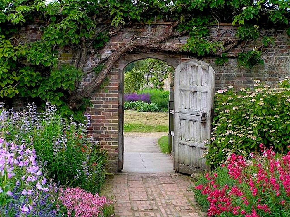 Secret garden an old wooden door leads into a garden for Garden door designs