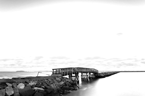 Plymouth, New England. USA. The harbour and the wooden bringe across the jetty. Black and white with high contrast blue filter | by Nicola Zingarelli