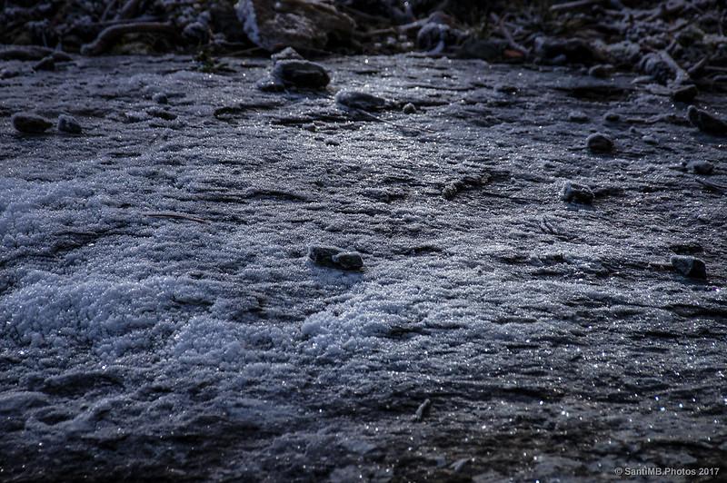 Destellos de luz del sol sobre roca helada por la escarcha