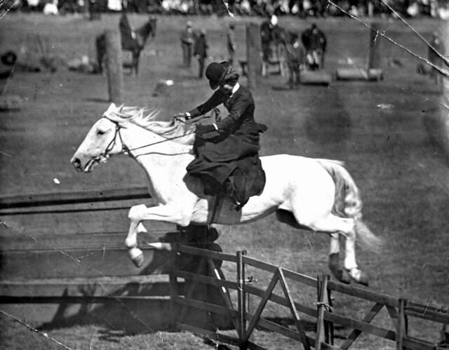 Horsewoman Riding Side Saddle Jumping A Fence At The Moont