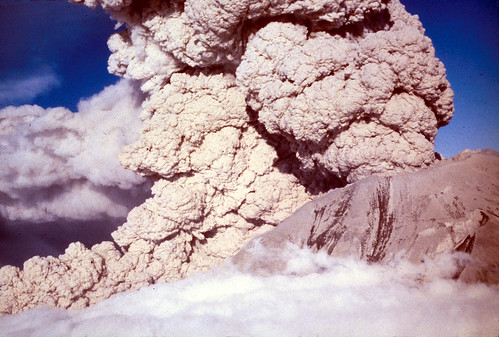 Another color aerial image, this one taken from a lower altitude, just above the clouds covering the valley floor. From this angle, both the taller eruption column and the shorter pyroclastic flow spilling from the gap in the crater wall are clearly visible. The ash-covered flanks of the volcano have dark streaks.