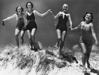 Young women running over a sand dune on an unidentified beach, ca. 1935 | by State Library of Queensland, Australia