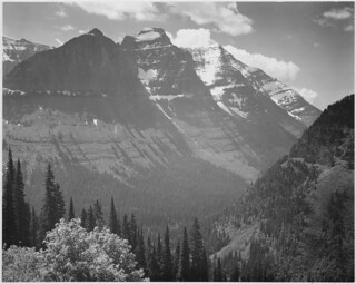 "Valley, snow covered mountains in background, ""In Glacier National Park,"" Montana. 