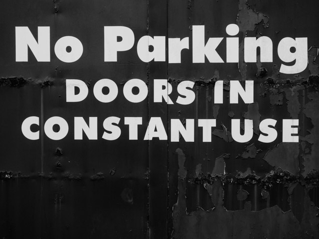 no parking signage on metal gates
