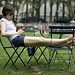 Girl with cell phone lounging in Bryant Park