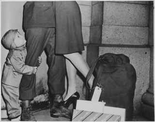 "A Youngster, Clutching His Soldier Father, Gazes Upward While the Latter Lifts His Wife from the Ground to Wish Her a ""Merry Christmas"" 