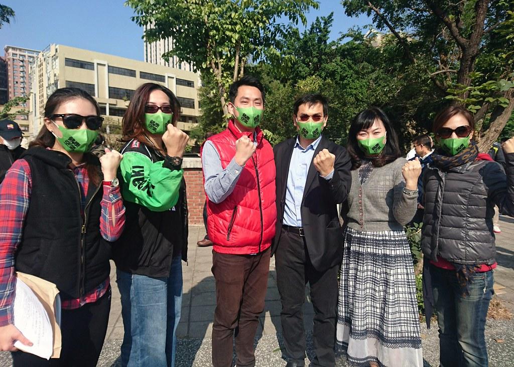 高雄市議員及助理戴上綠色口罩發起「簡單生存節」,要宜居不要移居。攝影:李育琴。