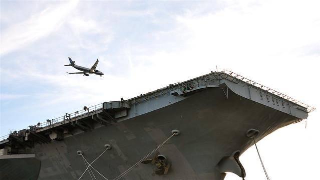 plane flying over naval ship