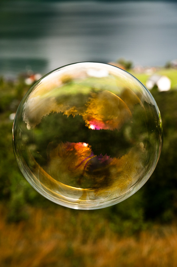 Morning light reflected in a soap bubble over the fjord ...
