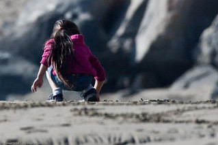 Cute little girl in pink sweater with long hair writes letters in the sand | by mikebaird