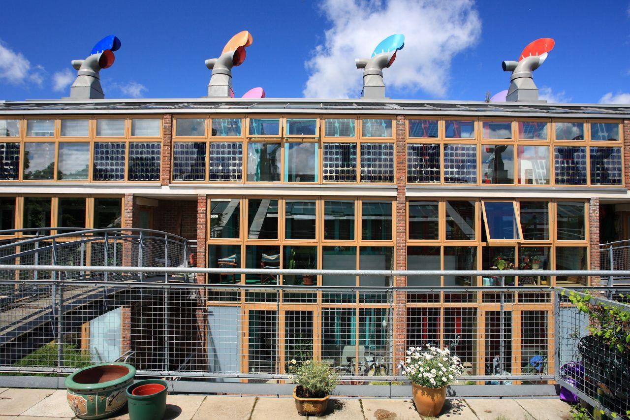 BedZED社區的建築識別元素:三層樓高的南向溫室、整合式太陽能光電板、彩色風杓。