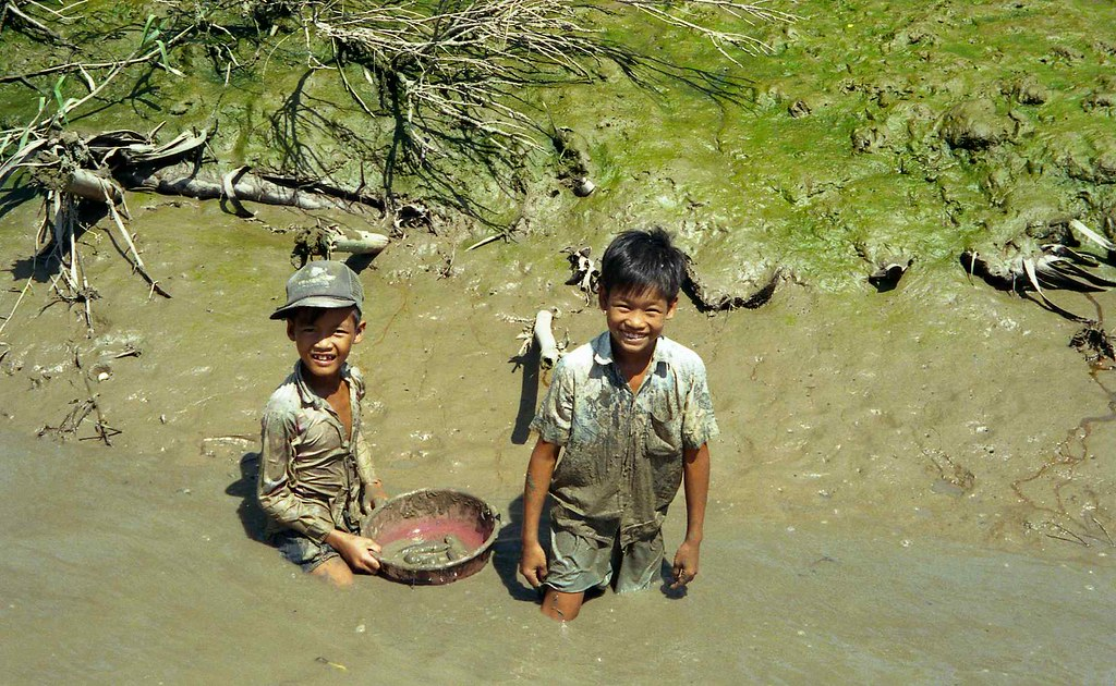 2 Boys Fishing In Mud Of Drained Pond Mekong River Delta