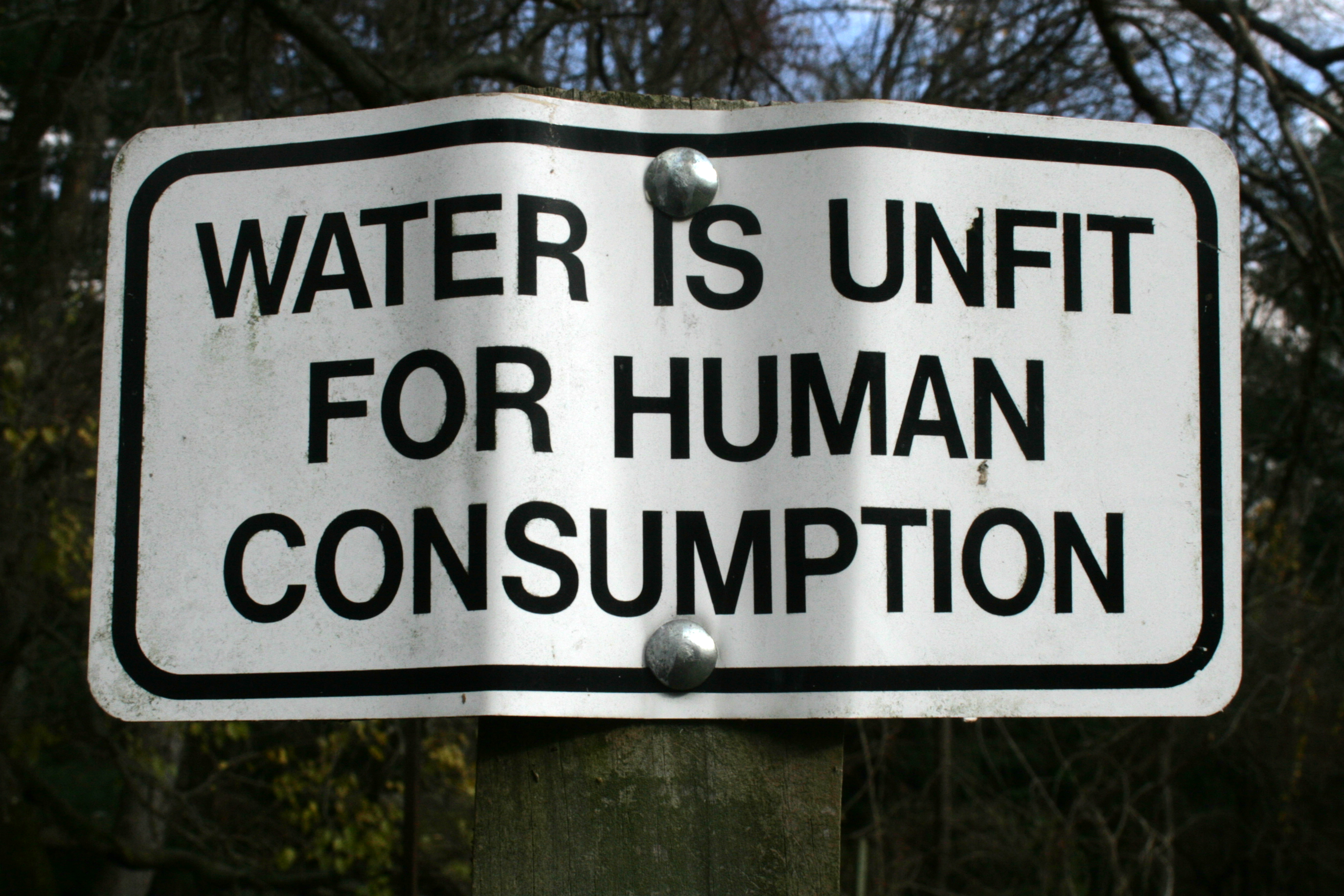 """Image of a large, dented black and white sign that reads, """"water is unfit for human consumption"""""""