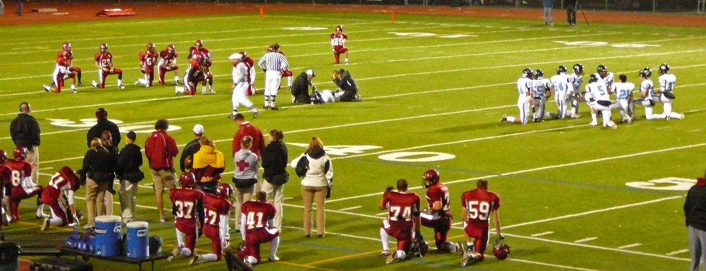 Image result for football kneels for injured player