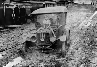 Boy sitting on the bonnet of a car bogged in mud from the 1925 flood at Innisfail, Queensland | by State Library of Queensland, Australia
