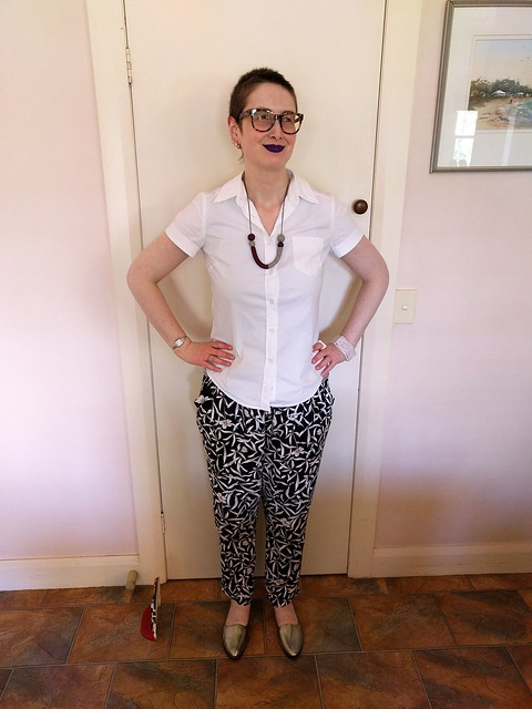A woman wearing a short sleeve white shirt and loose, floral print pants.
