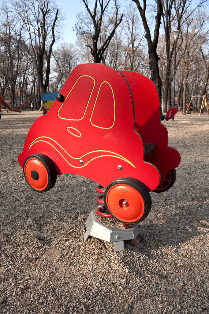 Red toy car on children's playground area | Bright red toy ...