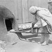 Anna Maria Toya placing bread in oven