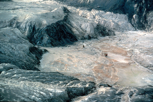 Color image shows a huge crater with ridges all around it. The only thing that tells us this isn't a moonscape is the fact the geologists standing inside it aren't wearing spacesuits, and there is stream erosion beginning in the crater floor.