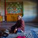Elderly monk spins prayer wheel in Qinghai, China.