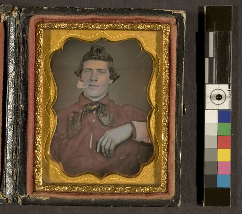 Portrait of young man in red shirt, smoking a clay pipe | by George Eastman House