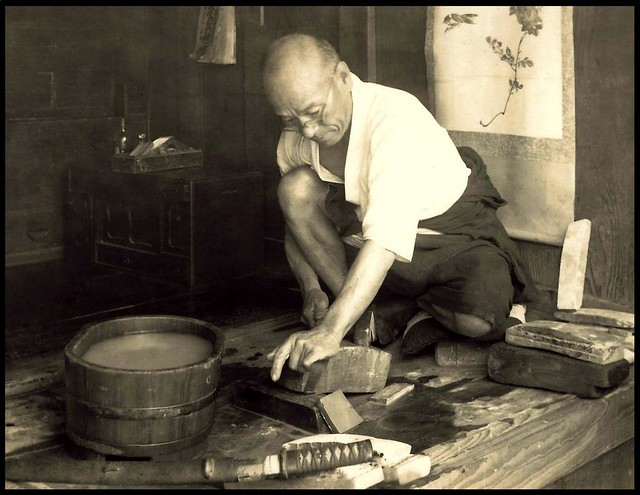 a swordsmith sharpens a blade in old japan the blade at