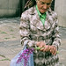 An elderly woman selling flowers
