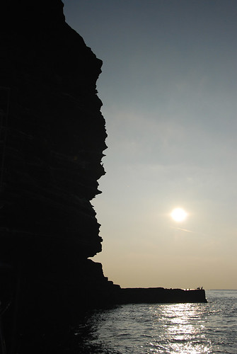 View of the sun setting on the Cliffs of Moher from the Aran Islands ferry