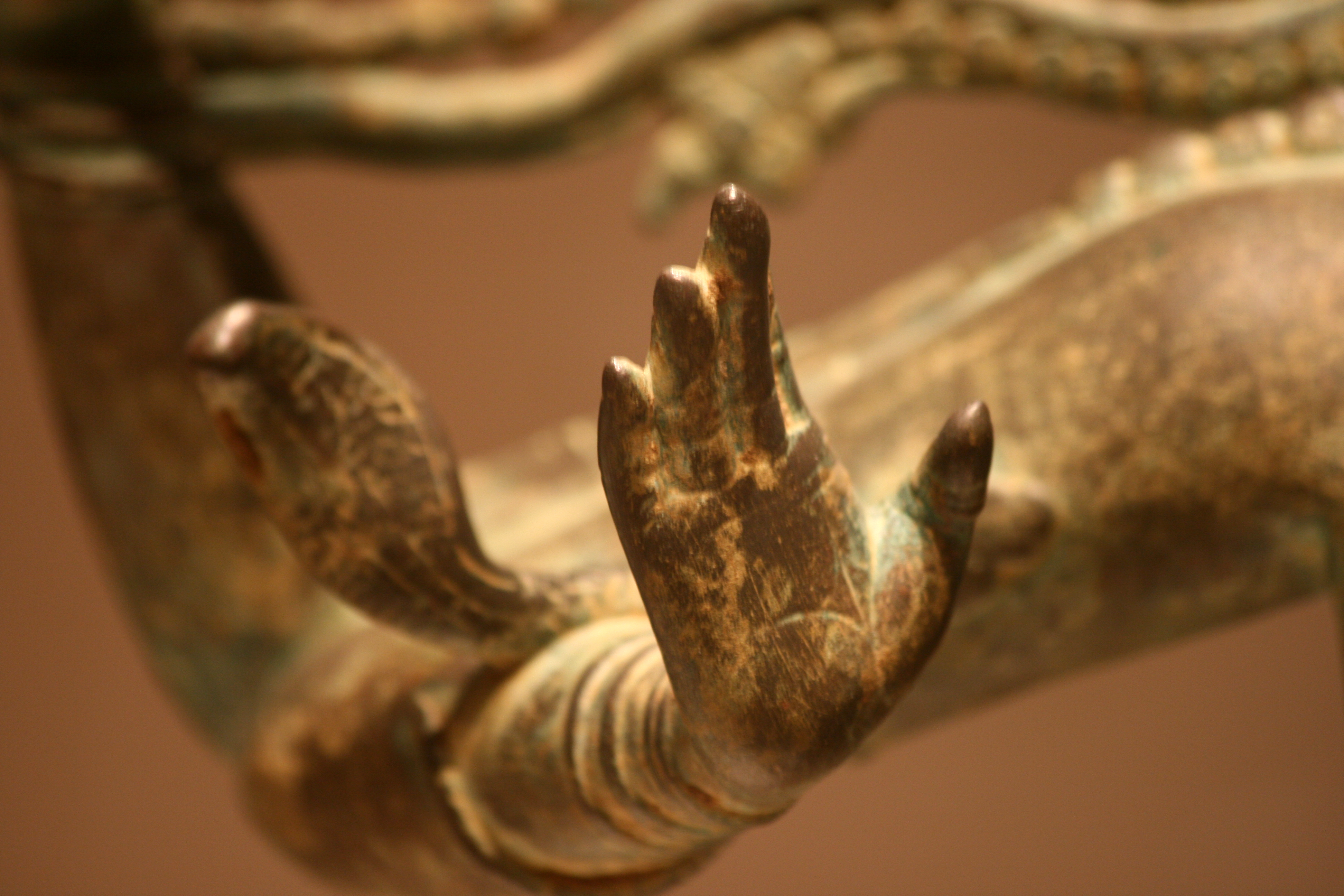 An image of a sculpted hand, in color, dominant sepia tones.
