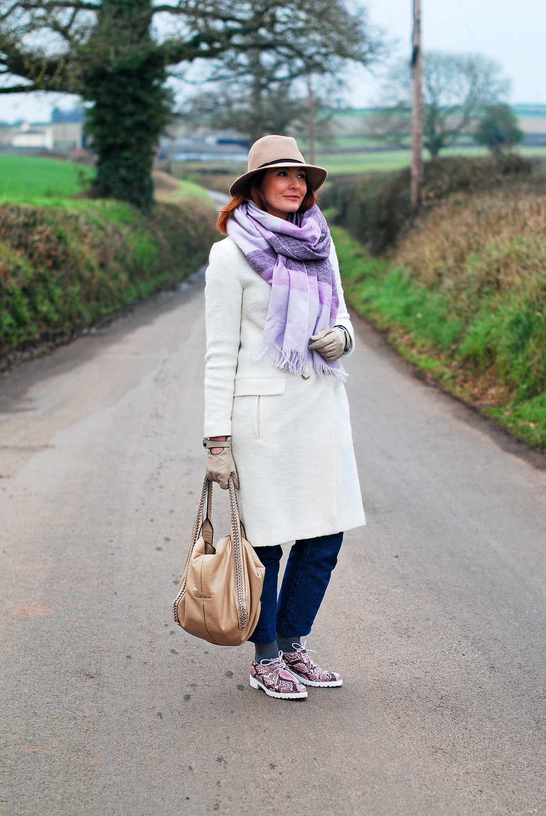 Cold weather outfit: Long white wool coat  oversized lilac scarf  camel fedora  dark wash boyfriend jeans  pink snakeskin lace up shoes | Not Dressed As Lamb, over 40 style