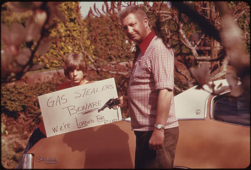 Country's Fuel Shortage Led to Problems for Motorists in Finding Gas as Well as Paying Much More for It, and Resulted in Theft From Cars Left Unprotected. This Father and Son, Made a Sign Warning Thieves of the Possible Consequences 04/1974 | by The U.S. National Archives