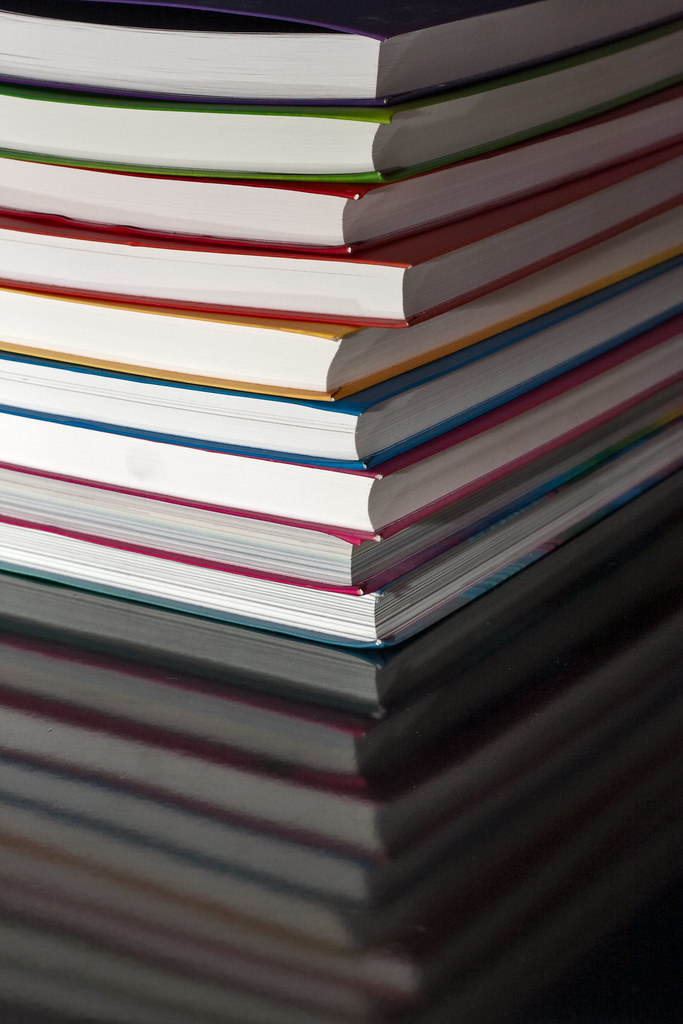 Stack of thin flexicover books on reflective table | Flickr