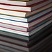 Stack of thin flexicover books on reflective table