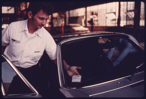 City Employee Affixes a Temporary 30-Day Sticker to the Windshield of a Car after It Had Failed Testing at an Auto Emission Inspection Station in Downtown Cincinnati, Ohio...08/1975 | by The U.S. National Archives