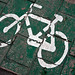 White bike sign on green tiled sidewalk