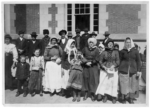 Photograph of Immigrants Outside a Building on Ellis Island | by The U.S. National Archives