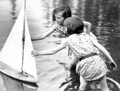 Two young girls reaching for a toy sailboat, Seattle, Washington | by UW Digital Collections