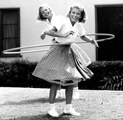 Two girls hula hooping in black and white