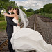 Bride and groom on railroad tracks with wind