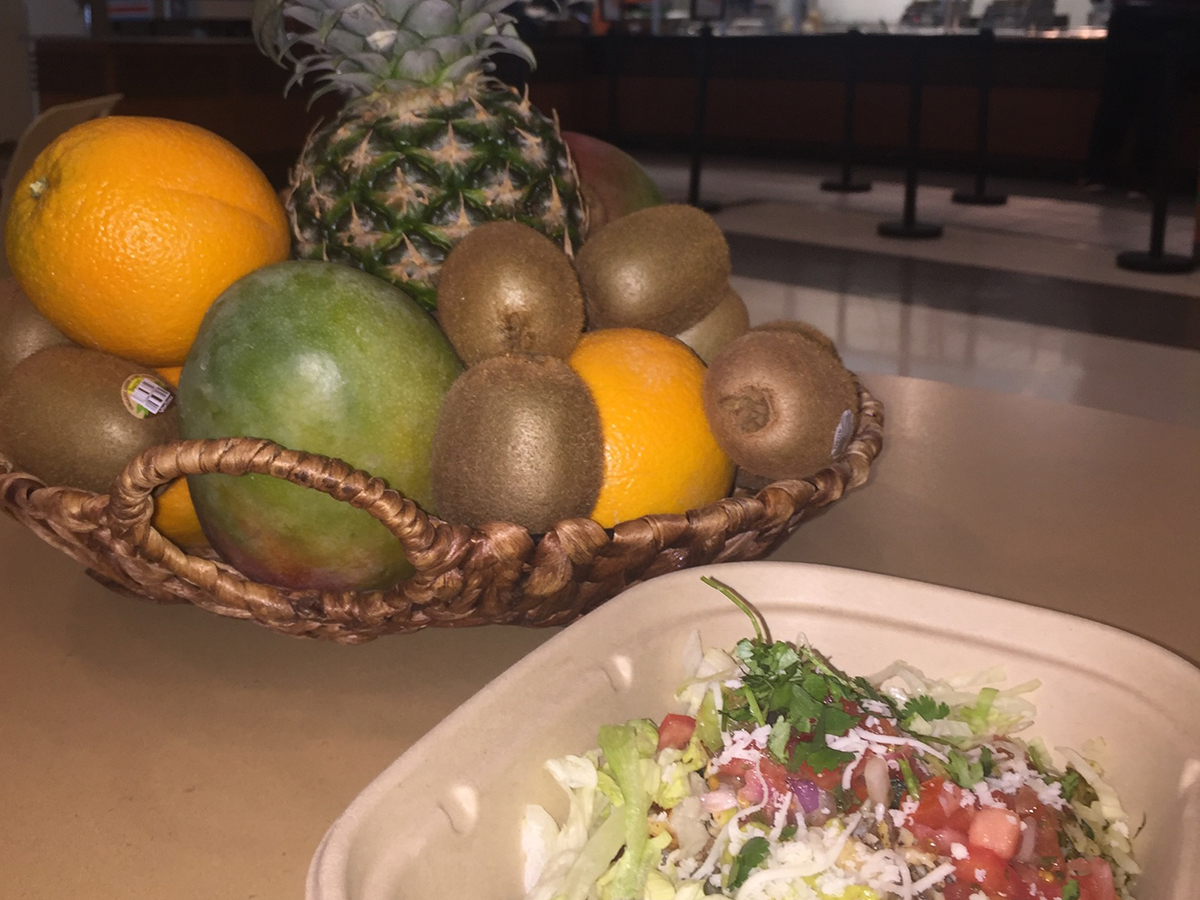 Salad in front of a basket of fruit.