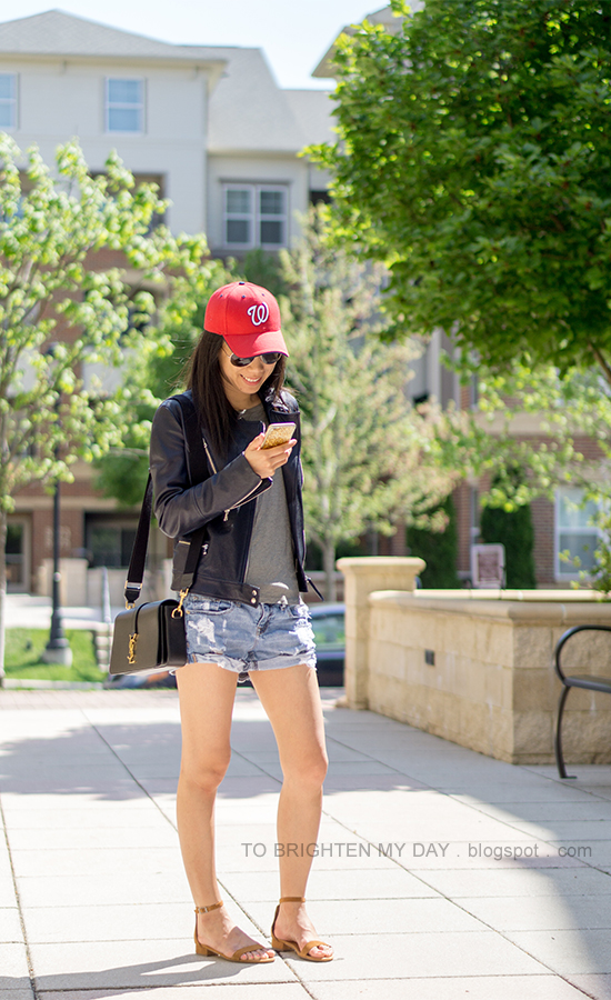 red baseball cap, black leather jacket, gray tee, distressed shorts, black shoulder bag, brown suede sandals