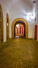 The hallways that run around the outside of the Seville Bullring. All of the arches have the same yellow trim like the outside of the building and the red is featured on the rails near the floor