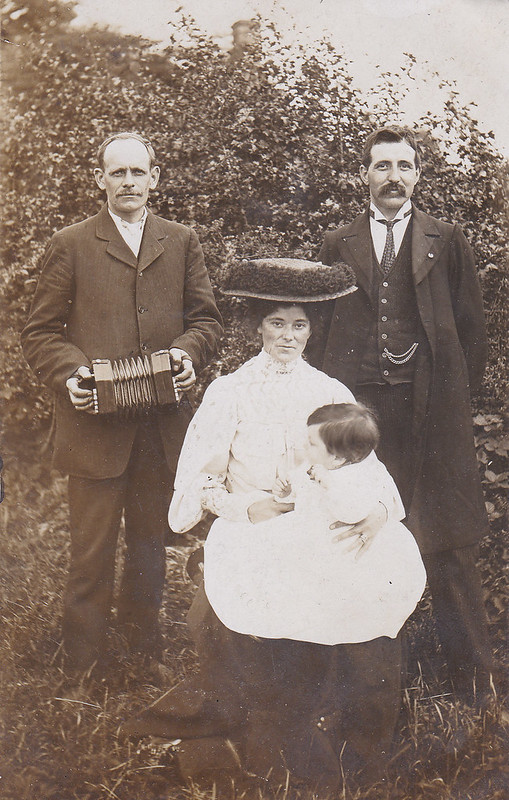 Early twentieth century photograph of two men, one with an anglo-concertina, and a woman holding a baby.
