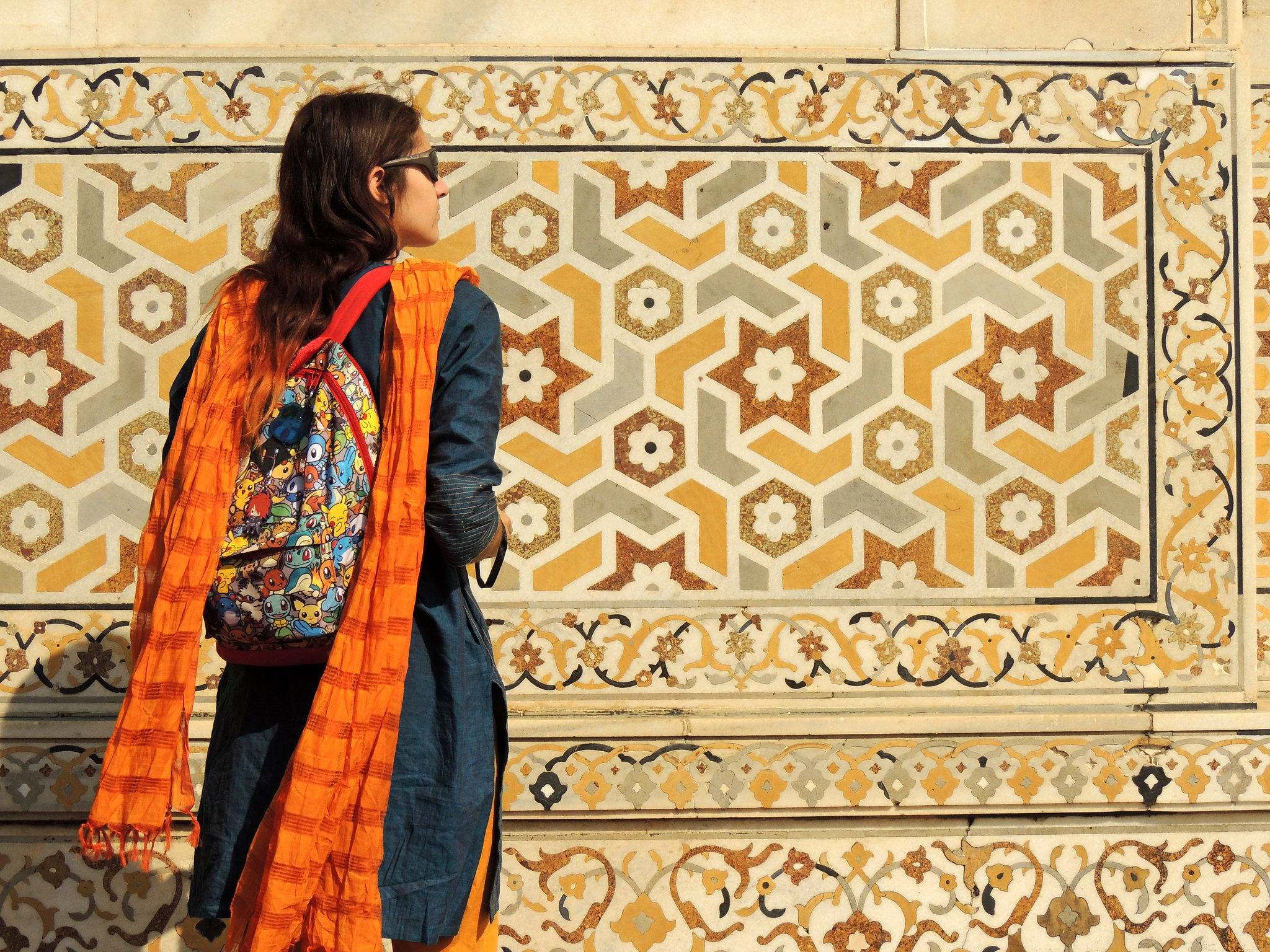 Image depicts a woman standing in front of a wall with geometric design marble inlay, at the Tomb of I'Timad-Ud-Daulah.