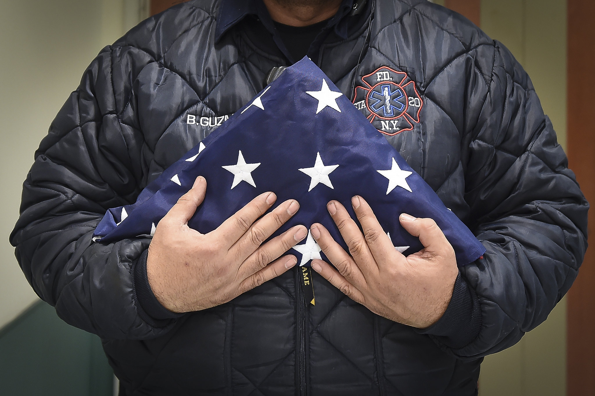 Benny Guzman of FDNY Station 20 in the Bronx holds a flag for a fallen EMT after a fatal incident during an evening shift on Thursday, March 16, 2017 in the Bronx, NY. Edwin J. Torres/Mayoral Photography Office