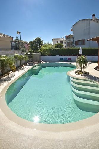 Piscina de arena con agua de color turquesa y plantas sa for Gunitec piscinas