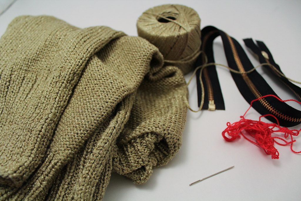a sweater, matching yarn, a zipper, needle and red embroidery floss are shown on a white background.